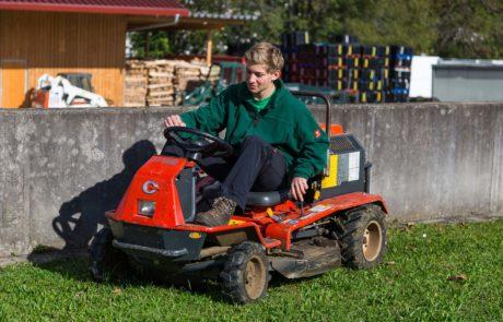 Mitarbeiter fährt Rasenmäher